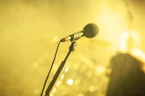 Microphone against yellow sparkling background lights — Stock Photo