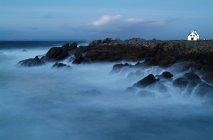 Casa di legno sul paesaggio roccioso in acqua blu dell'oceano, cielo crepuscolare blu — Foto stock