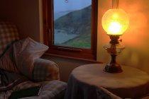 Soggiorno confortevole, lampada di cherosene sul tavolo in camera oscura con divano e libro — Foto stock