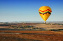 Hot air balloon flying above countryside fields — Stock Photo