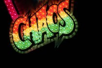 Illuminated colorful neon lettering chaos at night — Stock Photo