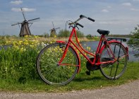 Red bicycle in farm field with windmills — Stock Photo