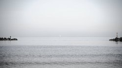 Sailboat on horizon in sea, scenic water surface — стоковое фото