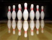 Cônes de bowling blanc sur surface brillante en bois avec réflexion — Photo de stock