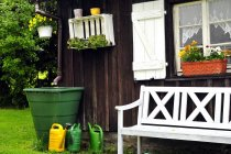 Wooden village house exterior with bench, watering cans and plants — Stock Photo