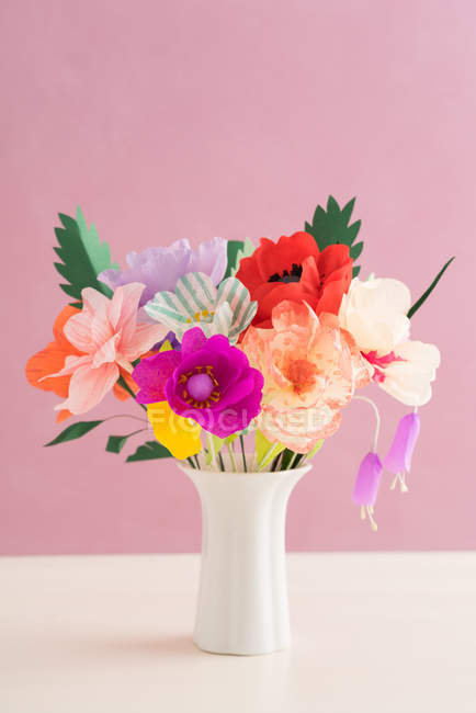 Creative colorful paper flowers bouquet in vase, pink background — Stock Photo