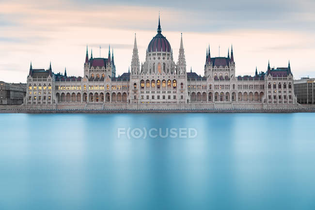 Blue river water of Danube and houses of parliament in Budapest, hungary — Stock Photo