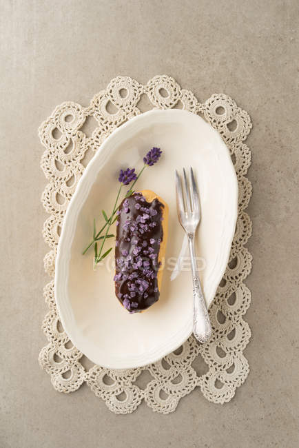 Chocolate frosting on eclair, cake plate with lavenders flowers — Stock Photo