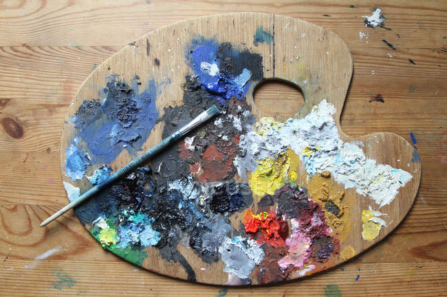 Colors palette with oil paint and brush on wooden floor surface — Stock Photo