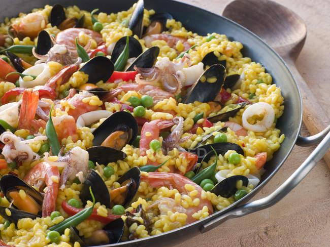 Traditionelle Paella-Pfanne mit Reis und Fisch und Meeresfrüchte am Tisch — Stockfoto