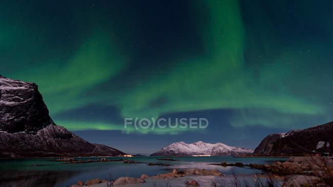 Cordilheira de Noruega com lago e aurora boreal luzes verdes no céu azul, luzes polares — Fotografia de Stock