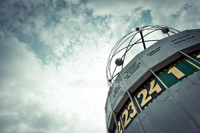 Reloj del mundo en Berlín contra el cielo nublado - foto de stock