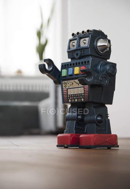 Retro robot de juguete en planta en la habitación - foto de stock
