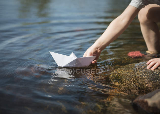 Partial view of child hand playing with paper boat at rover water — Stock Photo