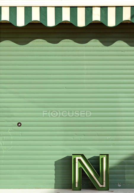 Closed green striped shutters door and old fashioned shop, letter N — Stock Photo