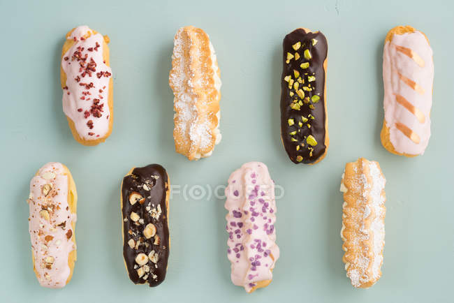 Different colorful eclairs, food background — Stock Photo