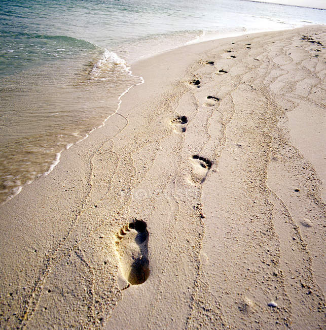 Footprints on sandy beach at sea water — Stock Photo