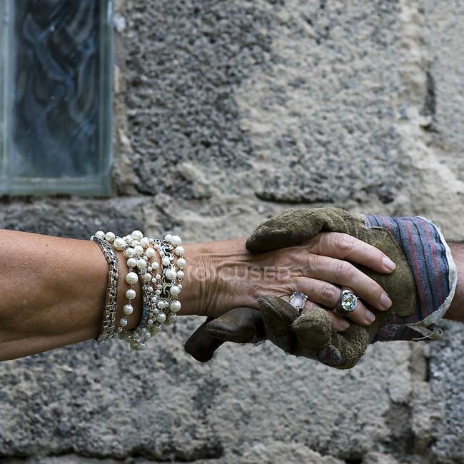 Рукопожатие, богатая женщина с браслетами, пожимая руку мужчина с перчатка — стоковое фото