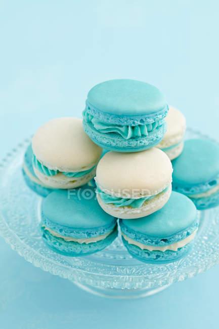 Бірюзові мигдалеве печиво, французький macarons на скляному столі торт — стокове фото
