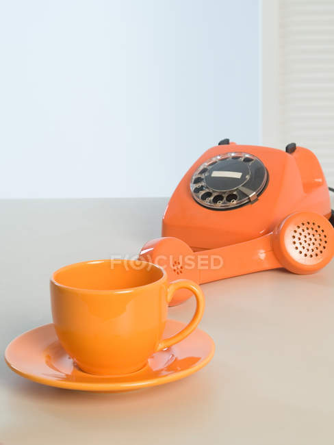 Old fashioned orange rotary phone and cup with plate — Stock Photo