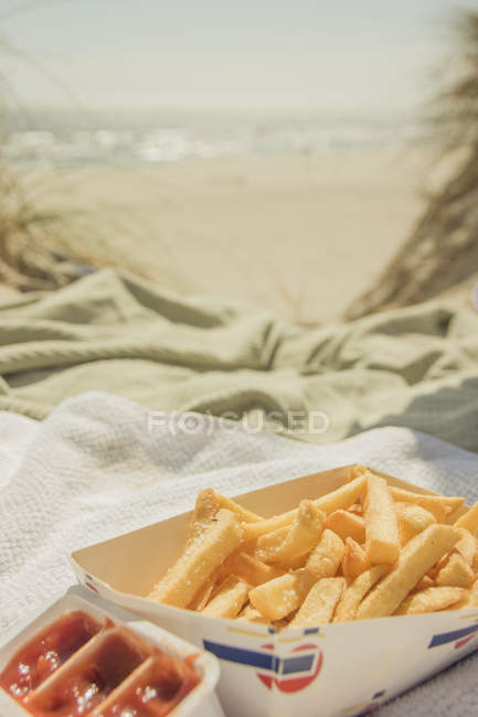 Fast food, french fries in take away box on the beach seaside — Stock Photo