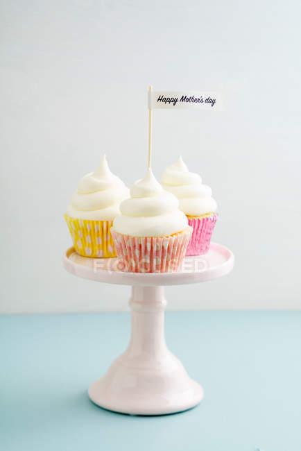 Cupcakes avec crème au beurre sur le stand de gâteau, bonne fête des mères — Photo de stock