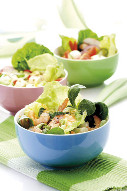 Mixed salads with basil leaves and shrimp, seafood in bowls — Stock Photo