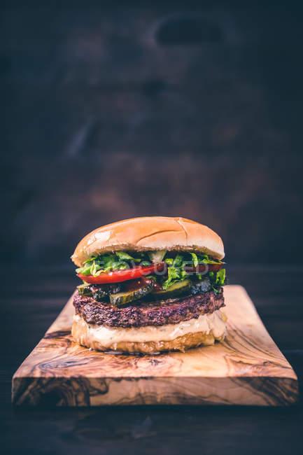 Restauration rapide, savoureux gros cheeseburger sur planche de bois — Photo de stock