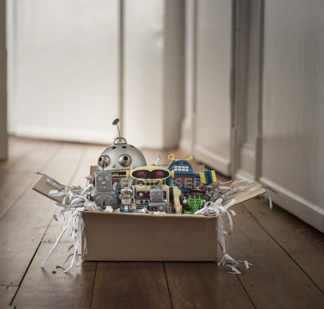 Childhood retro toys, robots in cardboard box — Stock Photo