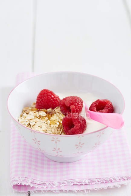 Cereal oatmeal with heap of fresh raspberries and pink spoon — Stock Photo