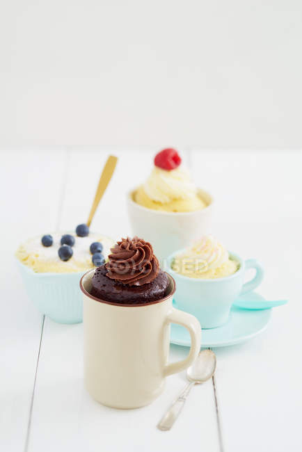 Various mug cakes in cups on table — Stock Photo