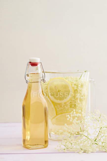 Frascos de vidro com calda e rodelas de limão em limonada — Fotografia de Stock