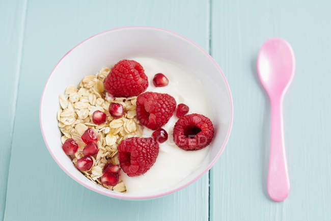 Harina de avena cereales con montón de frambuesas frescas, desayuno en la mesa con cuchara rosa - foto de stock