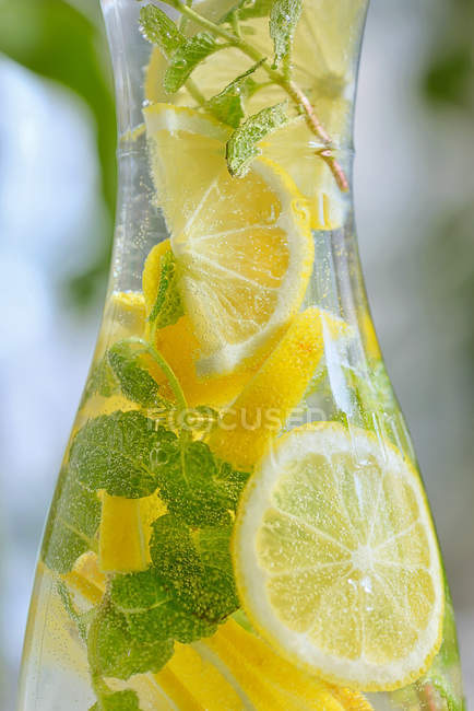 Glass bottle with lemons and mint lemonade — Stock Photo