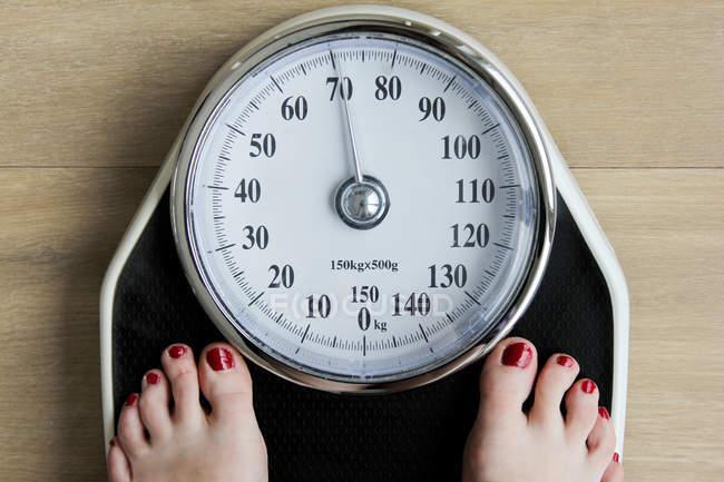 Vista dall'alto sui piedi in piedi sulla scala del peso, controllo del peso — Foto stock