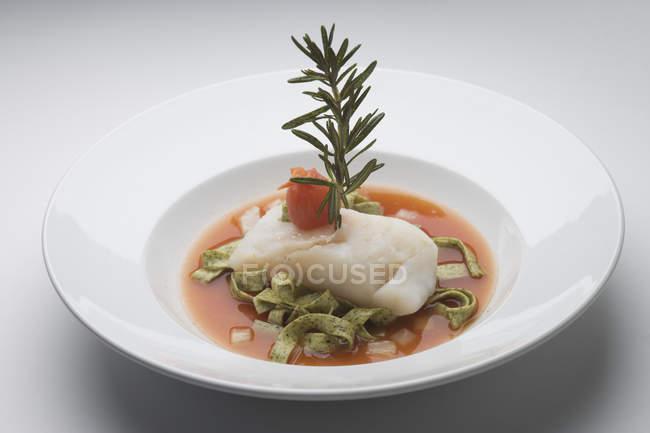 Pâtes aux épinards avec morue et romarin dans la sauce — Photo de stock