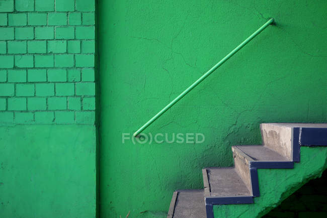 Staircase at green wall with railing — Stock Photo