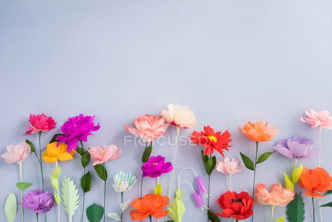 Fleurs en papier coloré créatif sur fond gris — Photo de stock