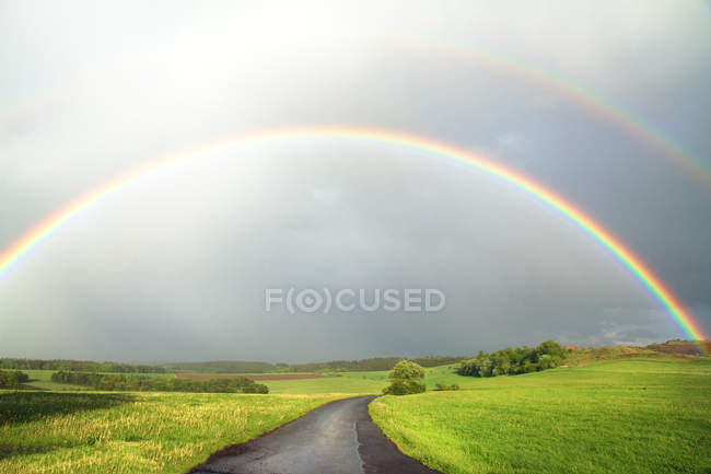 Rainbow over green field with road — Stock Photo
