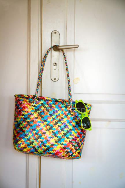 Bag with green sunglasses hanging on room door handle — Stock Photo