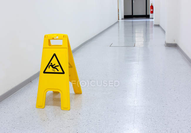 Yellow warning sign of slipping hazard in hallway — Stock Photo
