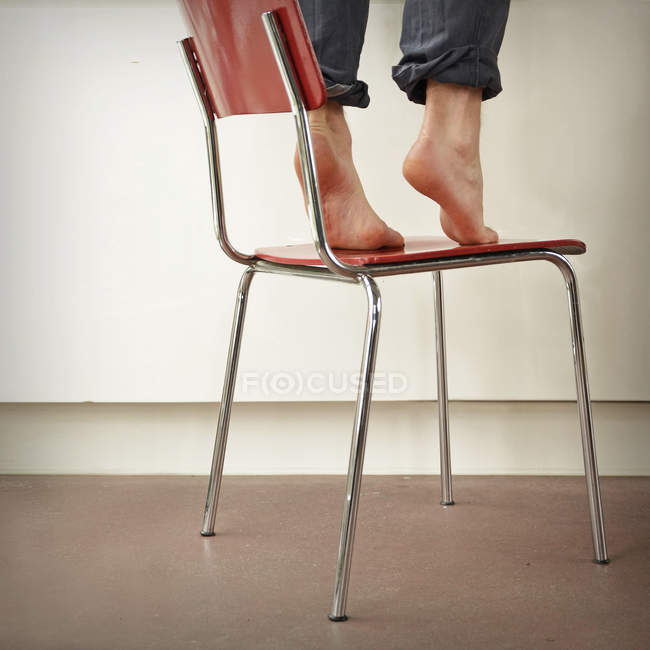 Cropped image of person barefoot feet standing on chair in room — Stock Photo
