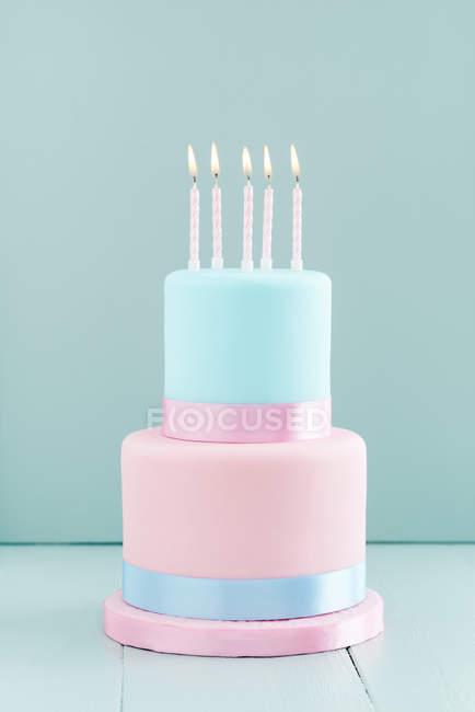 Помадной торт с зажженными свечами, два уровня торт — стоковое фото