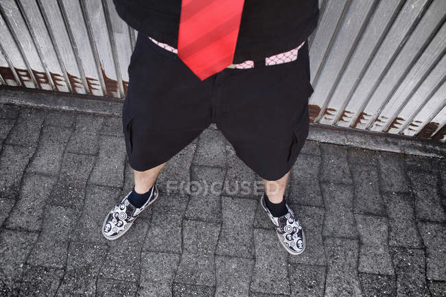 Stylish man wearing black shorts, shirt and red neck tie, partial view of person — Photo de stock