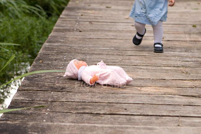 Doll lying on wooden pier, little child walking on footpath, — Stock Photo