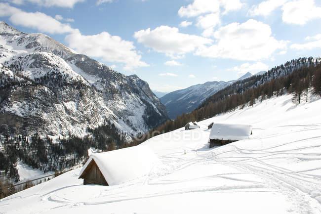 Bulletins d'enneigement des montagnes couvertes avec cabanes en bois — Photo de stock