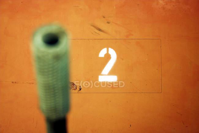 Parete arancione con numero due, messa a fuoco selettiva di 2 — Foto stock