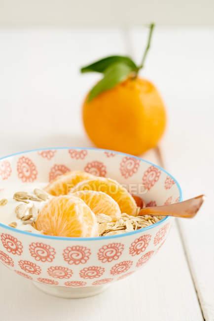 Fatias de tangerina com cereais na tigela — Fotografia de Stock