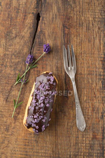 Деревянный стол с вилкой и шоколада глазурь на éclair, цветки лаванды — стоковое фото