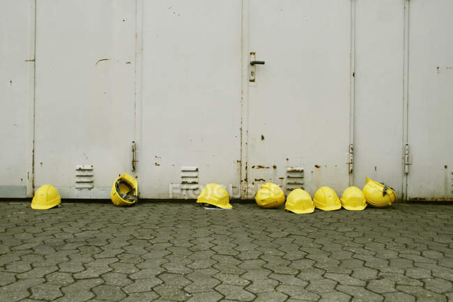 Labor protection, yellow helmets on floor outdoors at wall — Stock Photo